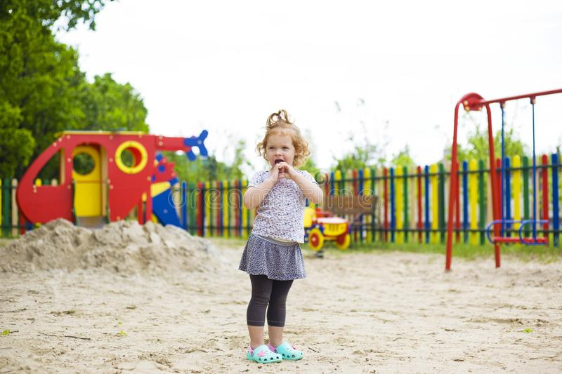 Cute little girl with red hair standing in the middle of the playground stock photos