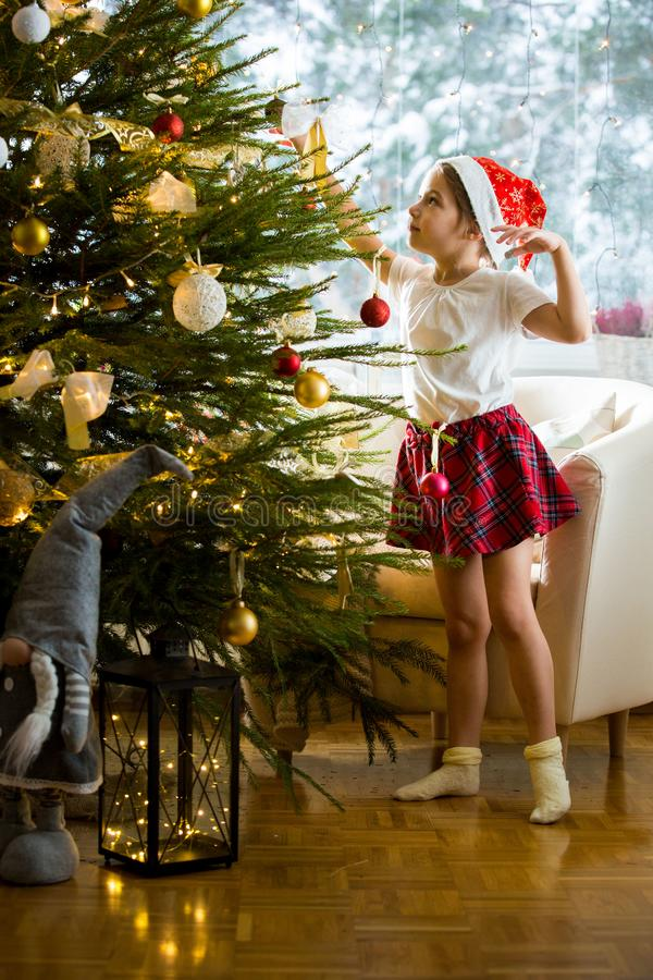 Cute little girl in red Santa hat and plaid skirt decorating Christmas tree at home stock images