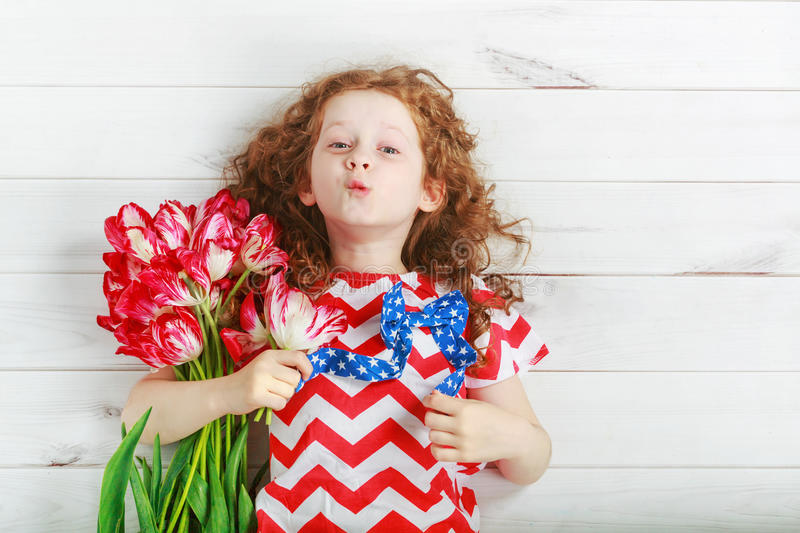 Cute little girl with red tulips on celebrating 4th july. Independence Day concept. royalty free stock images