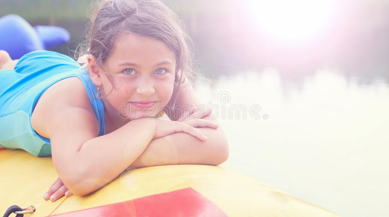 Cute little girl relaxing lying on inflatable mattress close-up portrait. stock photo