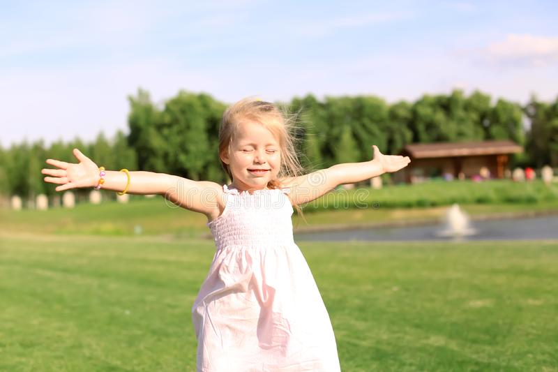 Cute little girl relaxing in park on sunny day royalty free stock photos