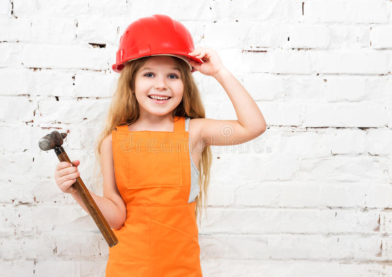 Cute little girl in repairman uniform and hammer in hand royalty free stock image