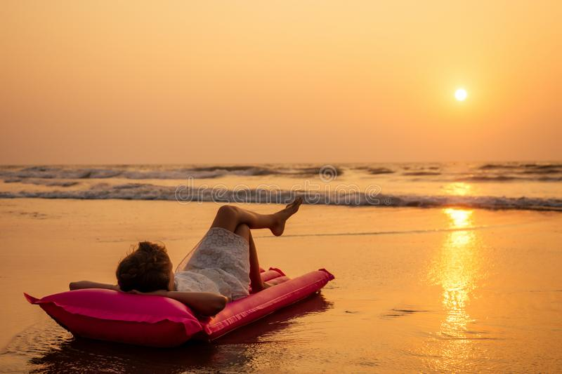 Cute little girl resting on inflatable mattress in summer vacation sunset beach tropical paradise sea ocean spf stock photo