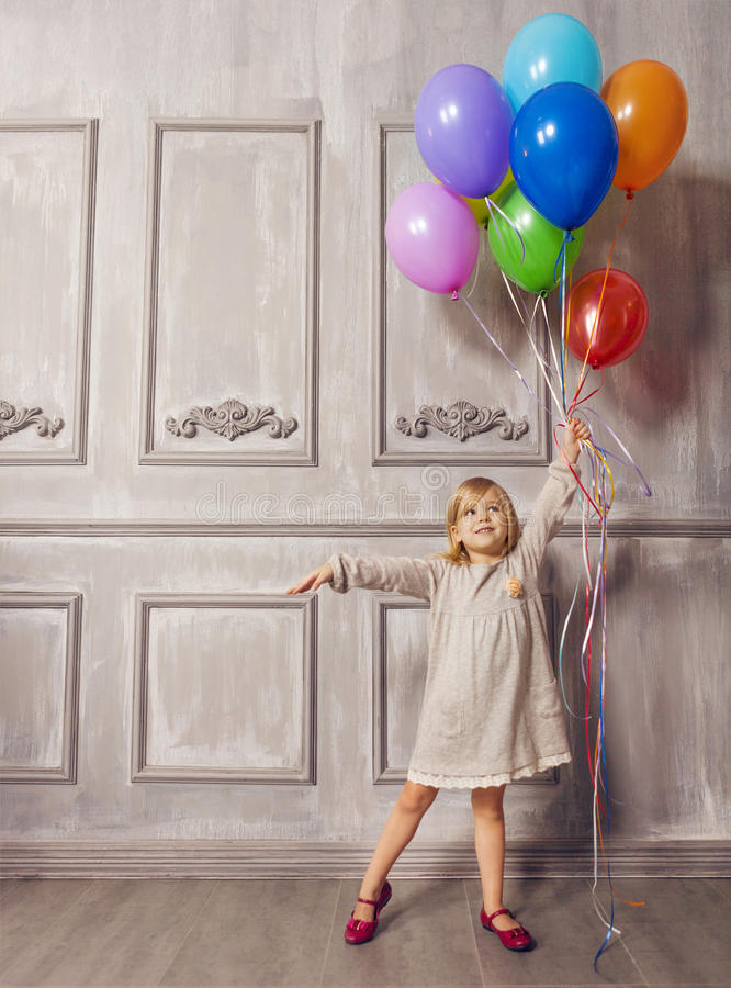 Cute little girl in retro style holding balloons royalty free stock photography