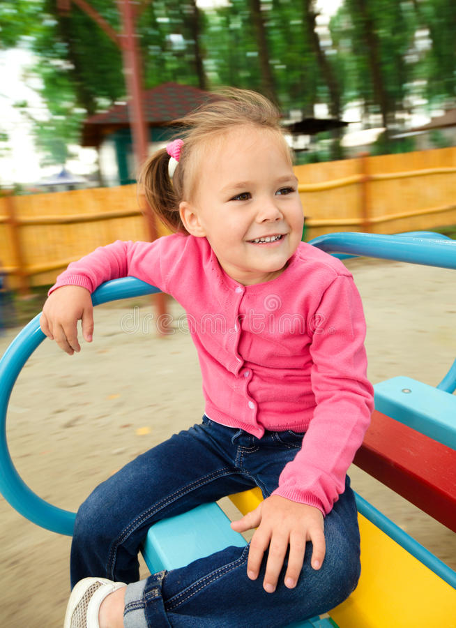 Cute little girl is riding on merry-go-round. Cute cheerful little girl is riding on merry-go-round, background blurred with motion royalty free stock photo