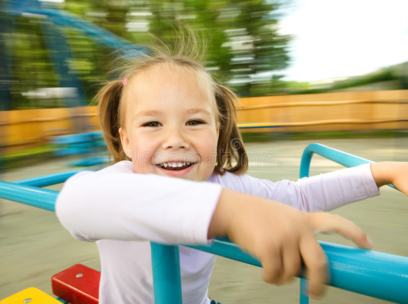 Cute little girl is riding on merry-go-round. Cute cheerful little girl is riding on merry-go-round, background blurred with motion stock image