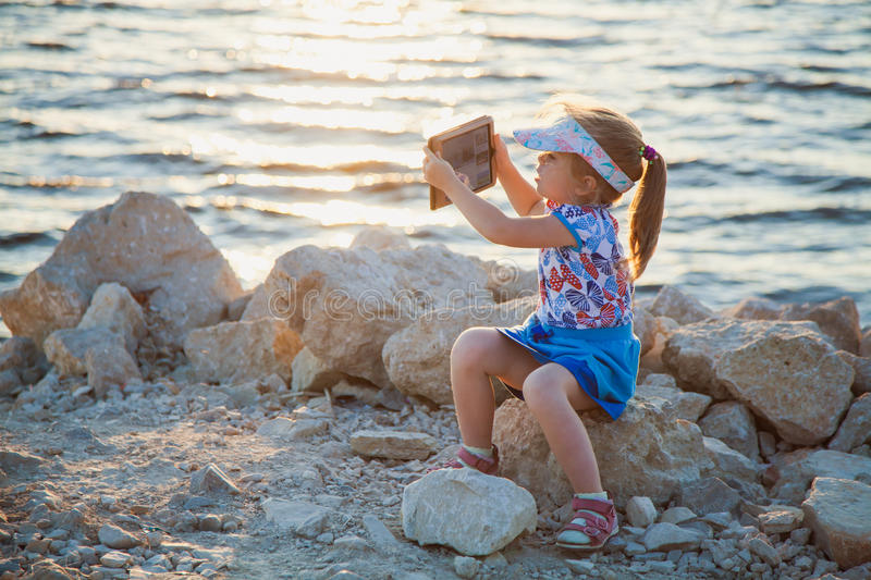Cute little girl on rocky beach with digital tablet royalty free stock image