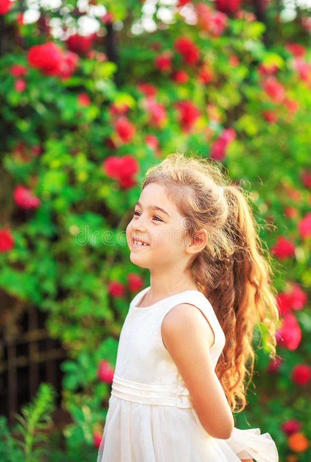 Beautiful little girl with roses in sunny summer park. Happy cute kid having fun outdoors at sunset royalty free stock photography