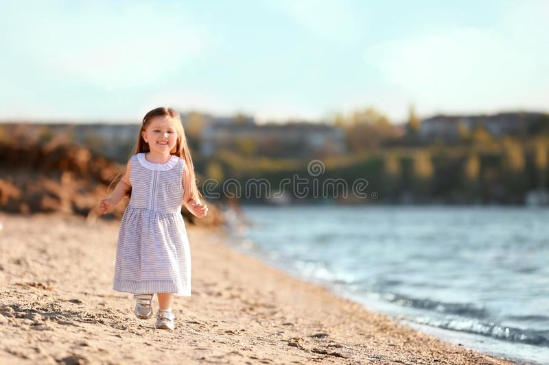 Cute little girl running along river bank royalty free stock photography