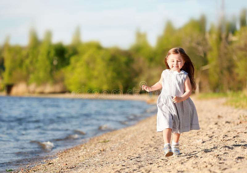 Cute little girl running along river bank. On spring day royalty free stock photos
