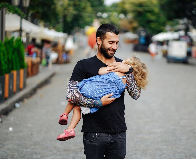 Cute little girl`s sleeping in her father`s arm. In the street stock photography
