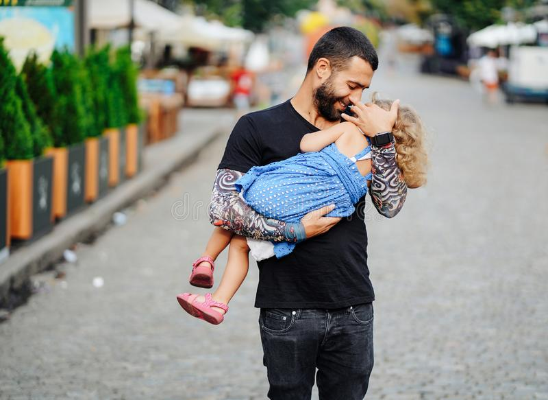 Cute little girl`s sleeping in her father`s arm. In the street royalty free stock photography