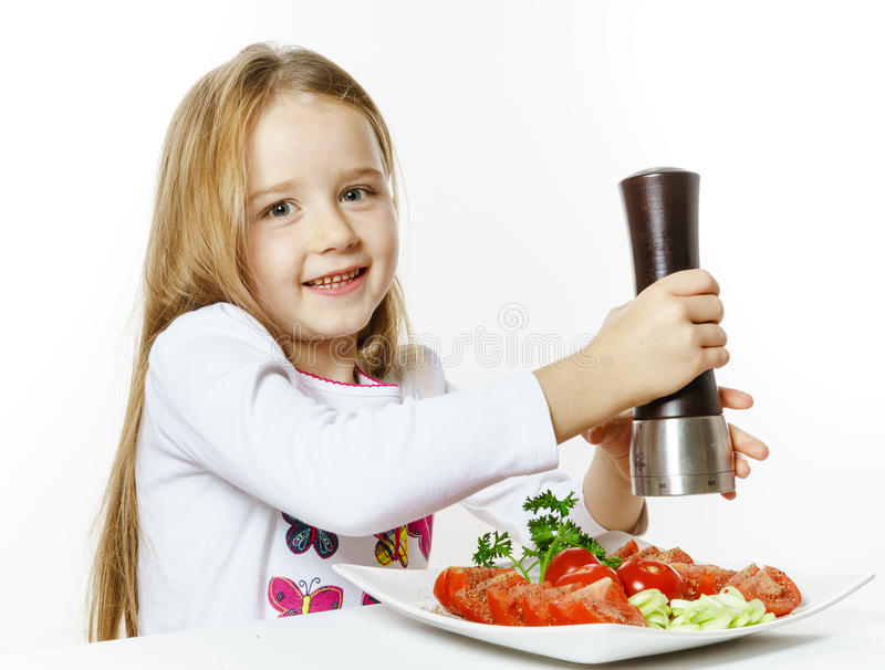 Cute little girl with salad and pepper box royalty free stock images