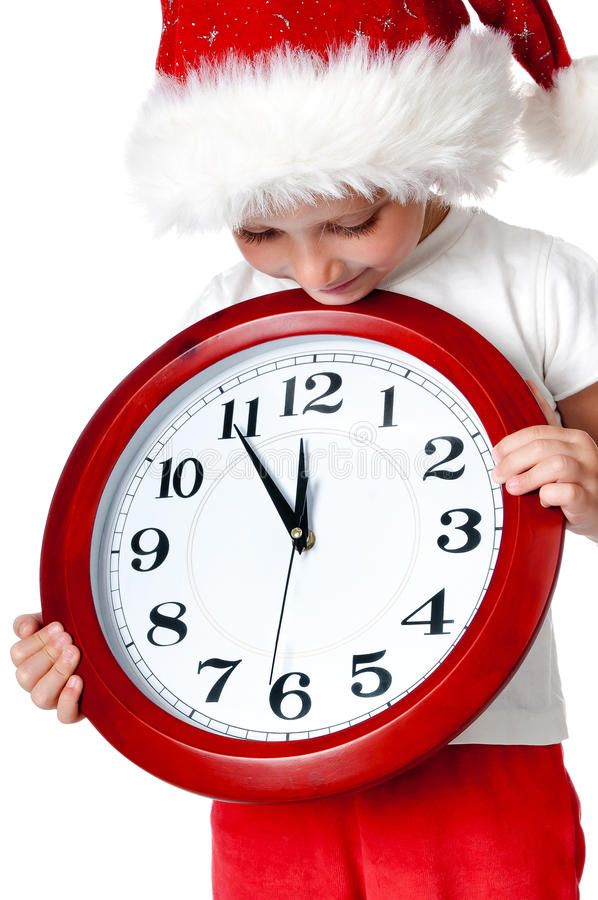 Cute little girl in santa cap with a clock. Isolated oin white royalty free stock image
