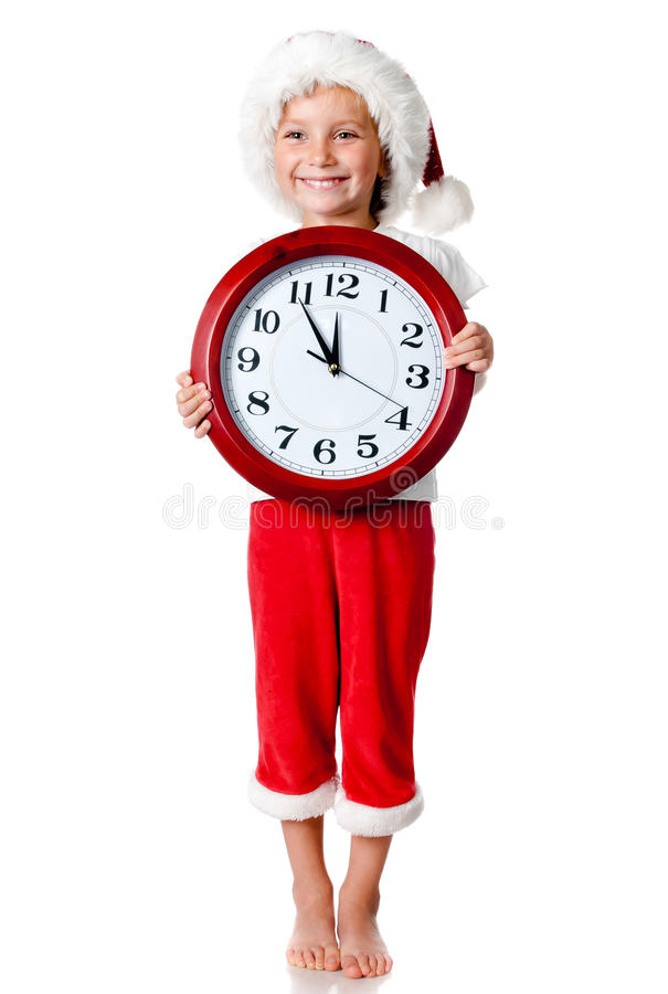 Cute little girl in santa cap with a clock. Isolated oin white royalty free stock photo