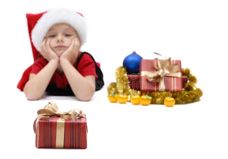 Cute little girl in a Santa Claus cap with Christmas gifts, isolated royalty free stock photography