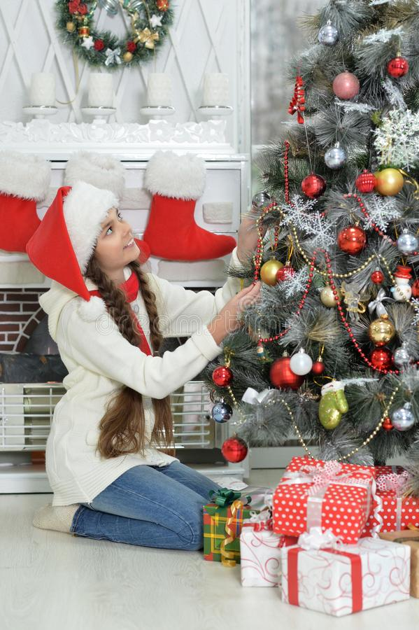 Cute little girl in Santa hat decorating Christmas tree stock photography