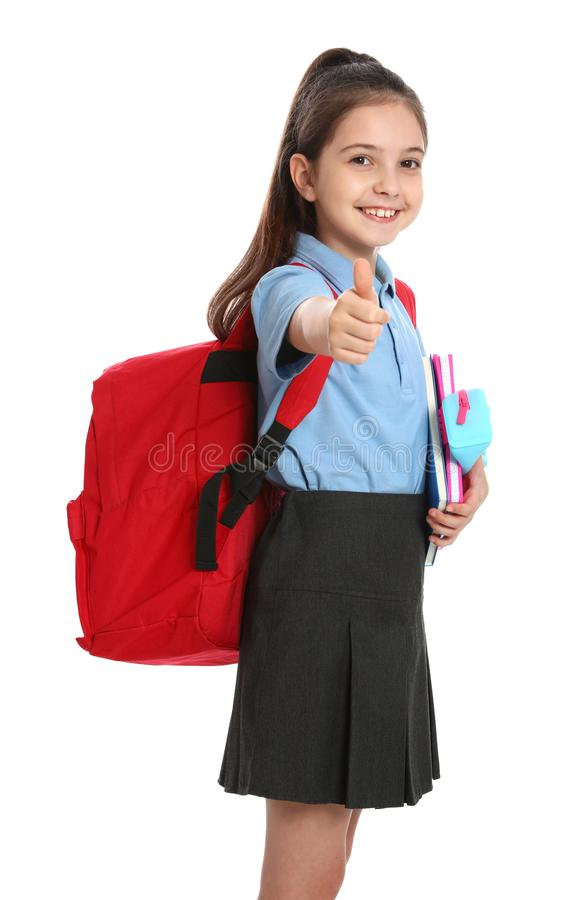 Cute little girl in  uniform with backpack and stationery showing thumbs-up on white background royalty free stock photos