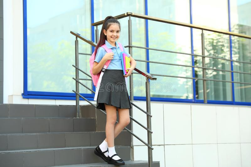 Cute little girl in school uniform with backpack and stationery on stairs royalty free stock photo
