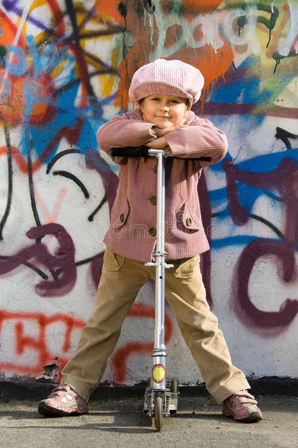 Cute little girl with scooter near graffiti wall royalty free stock photo