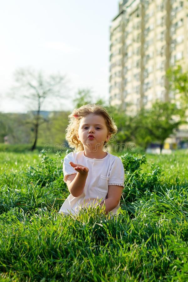 Cute little girl sending a kiss, sitting in the grass royalty free stock photos