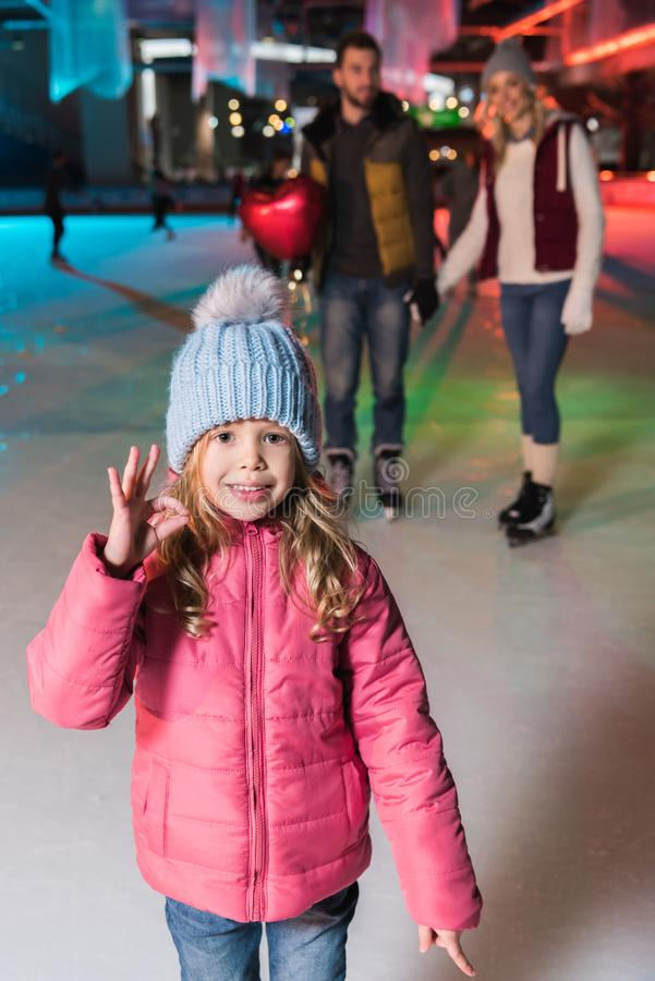 cute little girl showing ok sign and smiling at camera while ice skating with parents stock photo