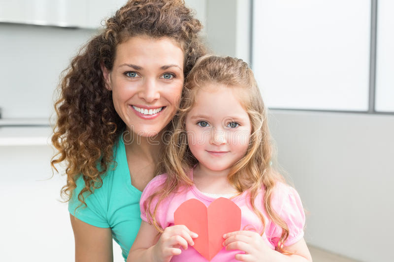 Cute little girl showing paper heart with mother royalty free stock image