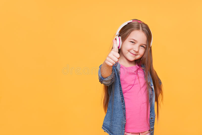 Cute little girl showing thumbs up one yellow background stock photo