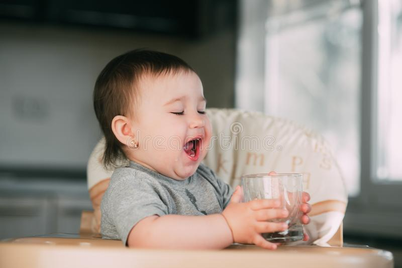 Cute little girl sitting in baby chair and drinking water royalty free stock photos