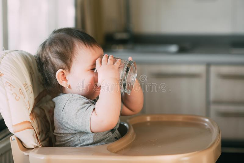 Cute little girl sitting in baby chair and drinking water stock image