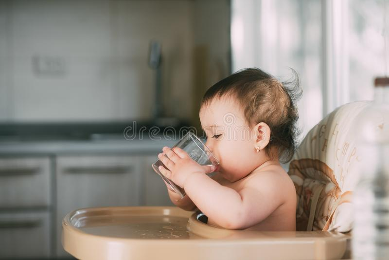 Cute little girl sitting in baby chair and drinking water stock images
