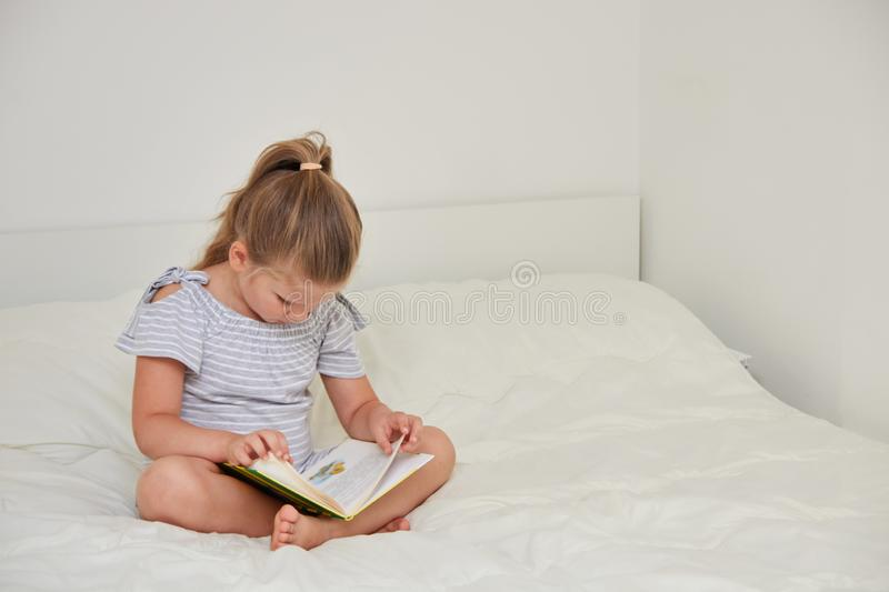 Little girl sitting on bed reading book royalty free stock photo