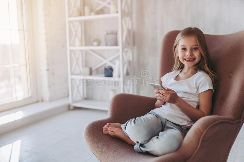 Little girl at home. Cute little girl is sitting in big chair at home with smart phone in hands, smiling and looking at camera royalty free stock photography