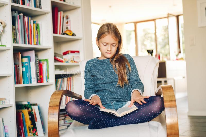 Cute little girl sitting in a chair at home and reading a book stock images