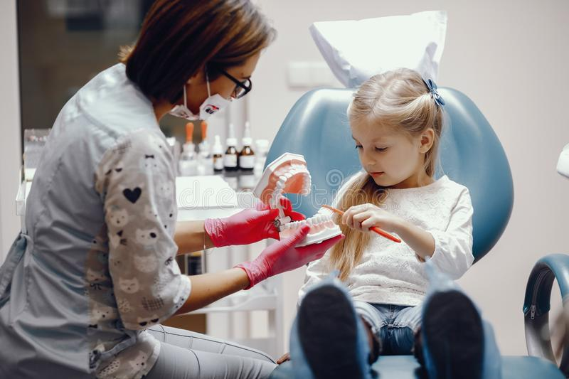 Cute little girl sitting in the dentist`s office. Little girl talking to the dendist. Child in the dentist`s office. Woman in a uniform stock photo