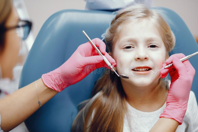 Cute little girl sitting in the dentist`s office. Little girl talking to the dendist. Child in the dentist`s office. Woman in a uniform royalty free stock image