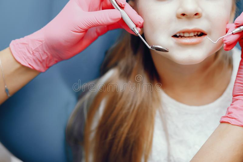 Cute little girl sitting in the dentist`s office. Little girl talking to the dendist. Child in the dentist`s office. Woman in a uniform stock image