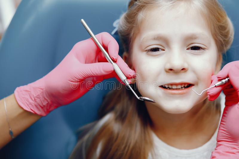Cute little girl sitting in the dentist`s office. Little girl talking to the dendist. Child in the dentist`s office. Woman in a uniform royalty free stock photos