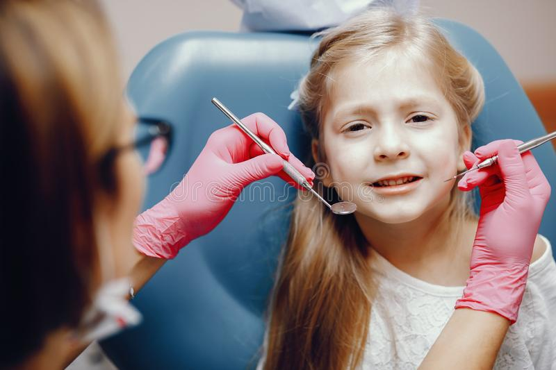 Cute little girl sitting in the dentist`s office. Little girl talking to the dendist. Child in the dentist`s office. Woman in a uniform royalty free stock images