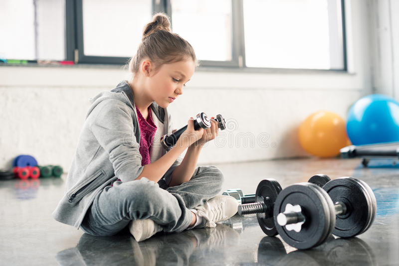 Cute little girl sitting on floor and exercising with dumbbells royalty free stock photo