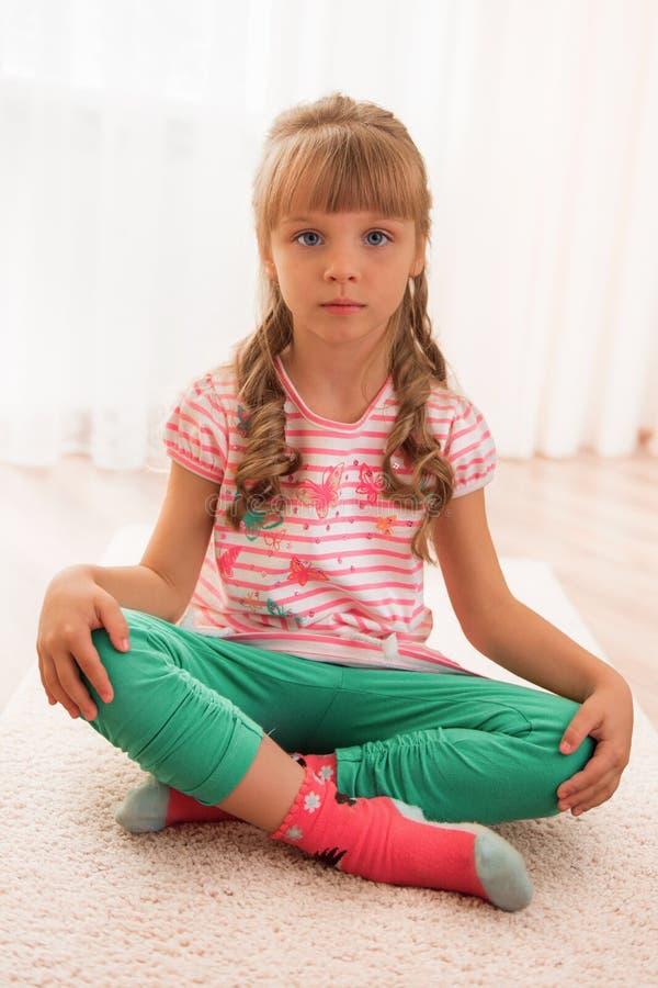 Cute little girl sitting on the floor royalty free stock photos