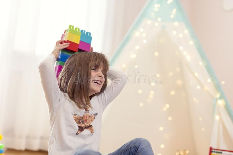 Cute little girl playing with building blocks stock photos