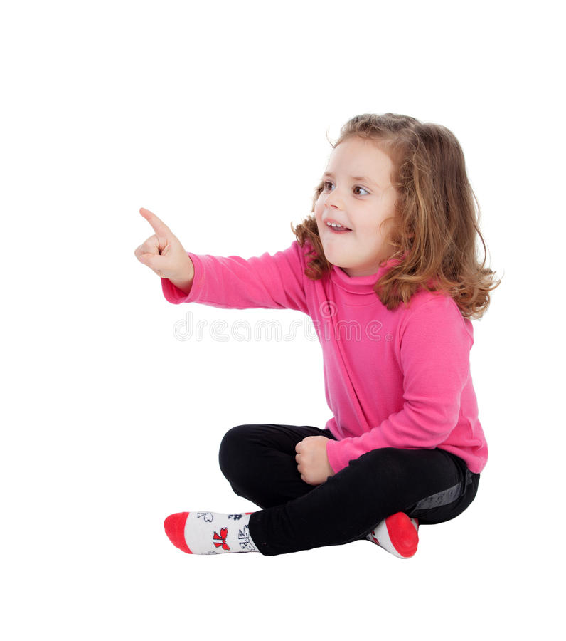 Cute little girl sitting on the floor pointing something with th royalty free stock photo