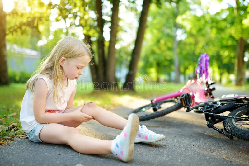 Cute little girl sitting on the ground after falling off her bike at summer park. Child getting hurt while riding a bicycle. stock image