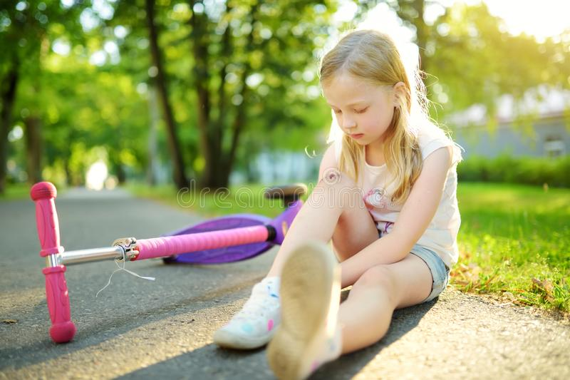 Cute little girl sitting on the ground after falling off her scooter at summer park. Child getting hurt while riding a kick scoote royalty free stock image