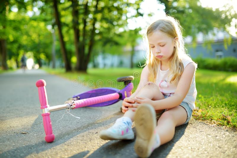 Cute little girl sitting on the ground after falling off her scooter at summer park. Child getting hurt while riding a kick royalty free stock images