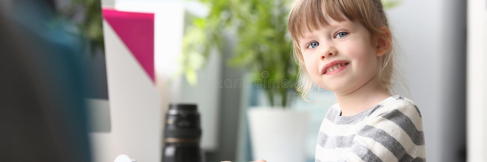 Cute little girl sitting at home at worktable looking in camera stock photography