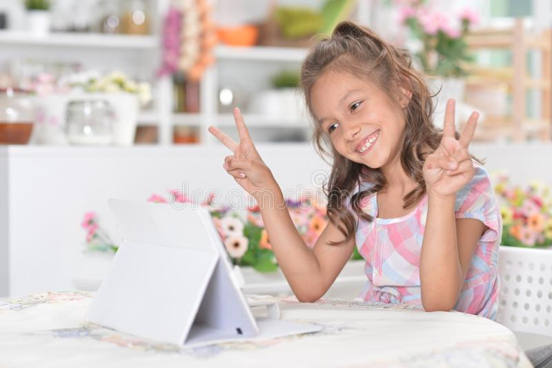 Portrait of cute little girl sitting at kitchen table in front of laptop and showing peace signs royalty free stock images