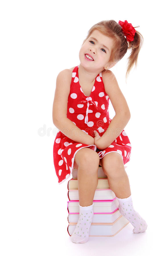 Cute little girl sitting on a pile of books royalty free stock images
