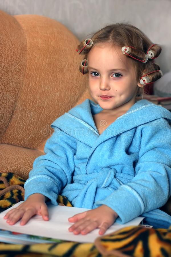 A cute little girl is sitting on the sofa in hair curlers on her head and dressed in blue bathrobe royalty free stock photos
